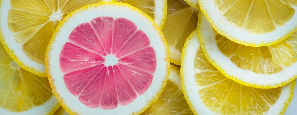 Stand out and get found depicted by pink grapefruit stands out in yellow grapefruit pile.